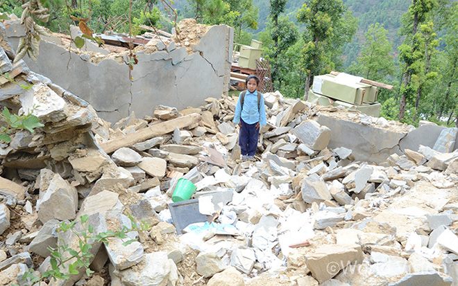 지난 2015년 네팔 대지진 당시 무너진 학교 건물 잔해에 서있는 아이의 모습(사진출처: 월드비전)