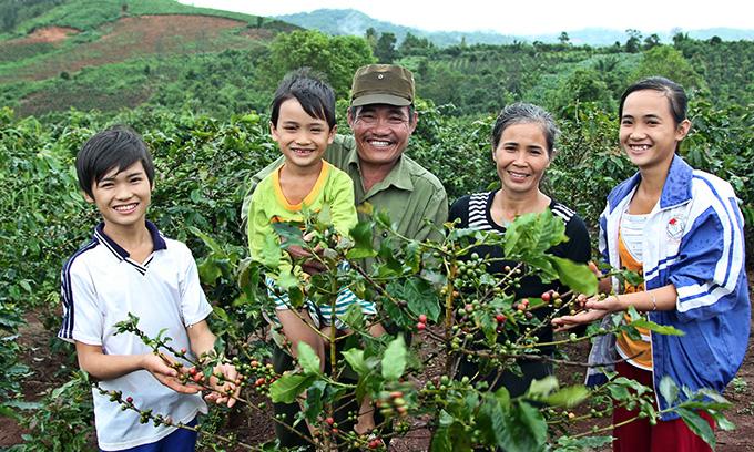 커피나무 앞에서 웃고 있는 민의 가족. 민의 아버지는 작년 월드비전 후엉호아 사업장에서 실시한 농업기술 역량강화 훈련에 참여해 커피생산량을 늘리는 기술을 배웠다.