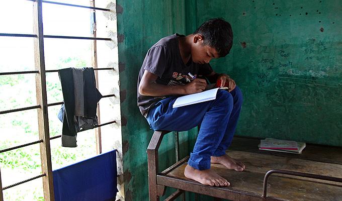 보통 사람이라면 5분도 못 버틸듯한 아슬아슬한 철근 위에 앉아 수학 문제를 풀고 있는 딥. 바낭 중학교 기숙사에는 학생들이 공부할 책상이 없을 정도로 학업환경이 매우 열악하다.