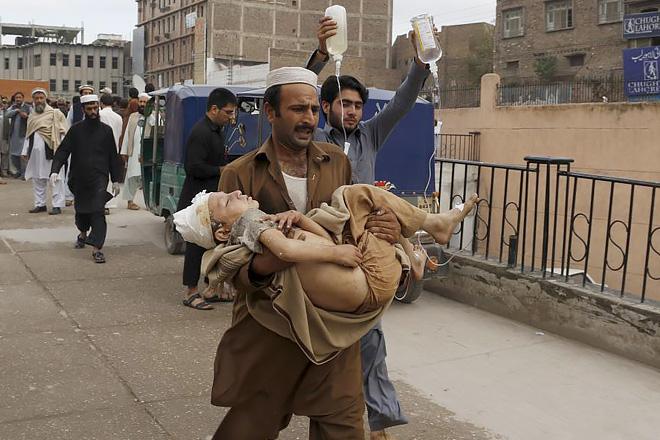 지진으로 부상당한 어린아이를 들고 병원으로 가는 모습(출처: 로이터스 통신사)