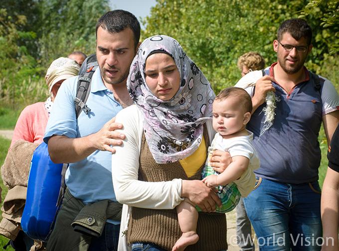 월드비전 직원과 함께 난민캠프로 이동중인 한 난민 가정과 8개월된 아기