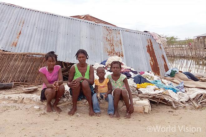 허리케인으로 무너진 집 앞에 주저앉아 있는 아이본과 그녀의 가족들(사진출처: 월드비전)