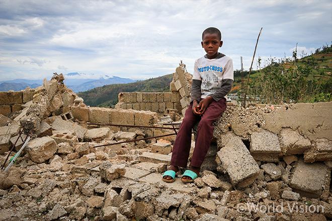 무너진 집 위에 앉아 있는 소년 앙비엥(사진출처: 월드비전)