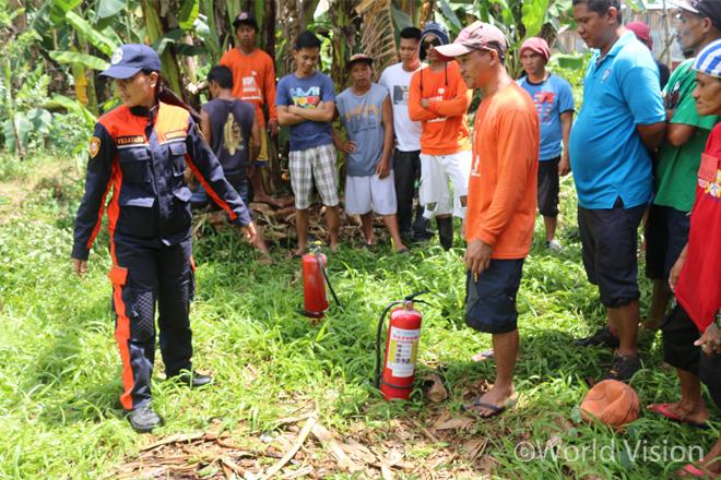 소방관으로부터 소화기 사용법에 대해 배우고 있는 마을 주민들의 모습(사진출처:월드비전)