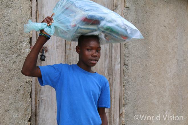월드비전 구호물자를 들고 가는 피에르(Pierre, 16세)의 모습(사진출처:월드비전)