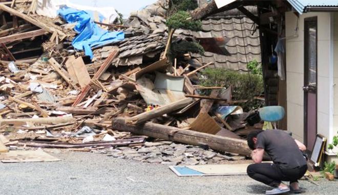 피해주민이 지진으로 인해 무너진 가옥 앞에서 좌절하고 있다(사진출처:BBC)