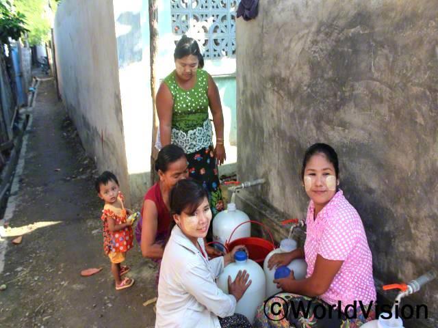 저희 지역사회 아동들은 깨끗하지 않은 식수 때문에 설사병에 시달리곤 했어요. 월드비전이 식수 저장못을 지역사회에 지원해 주고 먹어도 되는 물인지 식수 검사도 해줬어요. 이제는, 아이들이 설사병에 걸리지 않고 건강해요. -힌(세 아이의 엄마, 하얀 블라우스를 입은 사람)년 사진