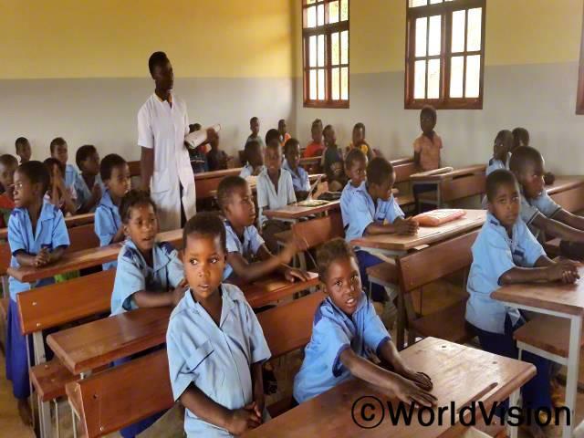 새로 지은 학교는 우리에게 학업의 원동력이 된답니다. 나무 밑에서 공부했을 때처럼 더러워지지도 않아요. 새 학교가 생겨서 정말 기뻐요. - 만얄로, 10세(맨 왼쪽 앞줄)년 사진