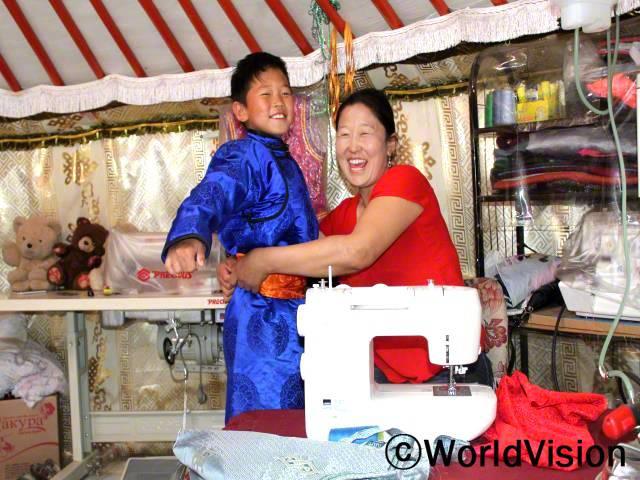 """""""아이들이 활짝 웃으면서 학교에 가요. 재봉틀 덕분에 소득이 생겨서, 아이들 교육지원과 가정 생계에 큰 도움이 되고 있어요.요즘에는 채소도 기르고, 과일 나무도 재배하고 있답니다."""" - 뭉크줄 이 가정은 재봉틀을 지원 받고 직업훈련에 참여하였습니다.년 사진"""