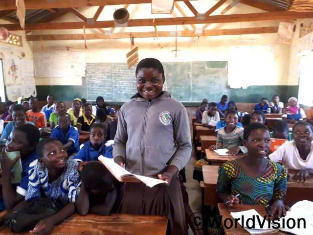 """""""전에는 교실이 없어서 비가 오는 날이면 수업을 듣기가 어려웠는데 후원자님 덕분에 교실이 생겨서 이제는 안전하게 공부할 수 있게 되었답니다."""" –마가렛(14세)년 사진"""