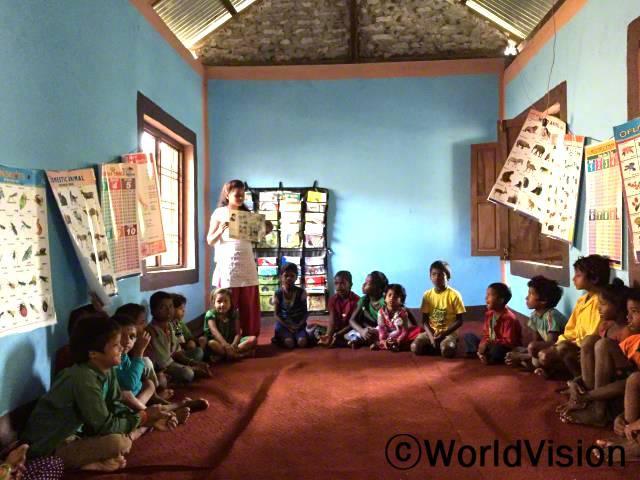 독서 캠프는 아이들에게 독서에 대한 흥미를 주었고, 이로인해 많은 학생들이 학교에 정기적으로 나오기 시작했어요. -마니타, 마을 자원봉사자 (서있는 사람)년 사진