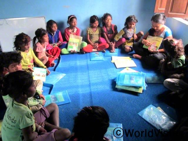 저희 지역사회의 아동들이 독서캠프를 통해 많은 도움을 받았어요. 아동들이 공부에 더 관심을 갖게 되었고, 읽기와 쓰기 실력이 좋아져요. -마누카(독서캠프 자원봉사자, 파랑색 원피스를 입은 사람)년 사진