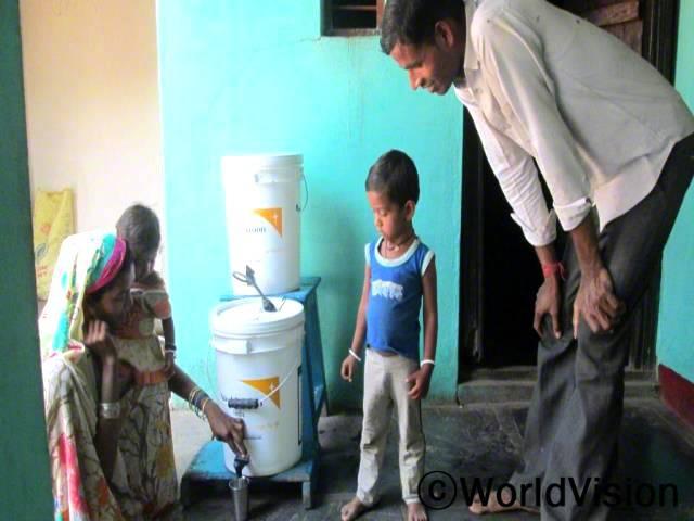 이제는 정수 필터를 사용하여 깨끗한 물을 마셔요. 깨끗한 물 덕분에 아이가 수인성 질병으로부터 보호되고 몸무게도 하루가 다르게 늘고 있어요. 저희 가족은 아프지 않고 아주 건강해요. -시닐, 아빠(23세). 월드비전은 지역개발사업의 일환으로 가정 136 곳에 정수 필터 136개를 지원했습니다.년 사진