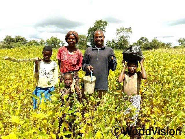 몇 년 전까지만 해도 농사 짓는게 어려웠어요. 월드비전이 마련해 준 여러 종류의 교육에 참여하면서 유기농법을 하는 리드 트레이너가 되었어요. 이제 가족들의 필요한 부분을 채워줄 수 있어요. -에녹(콩밭에서 가족들과 함께 서 있는 사람)년 사진