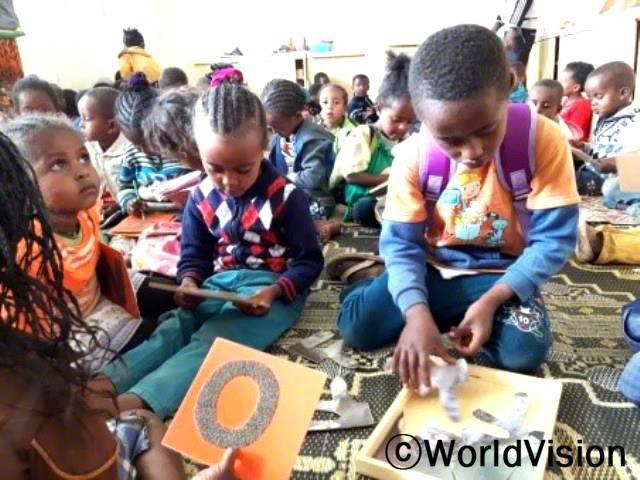 유치원이 생기기 전에는 주로 집에서 시간을 보냈어요. 지금은 친구들과 함께 책을 읽고 노래를 배우고 놀기도하며 시간을 보내요. -제리헌(5세), 오른쪽 오렌지색 티셔츠를 입은 아동년 사진