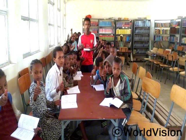 칼리드(15세, 빨간 티셔츠를 입은 아동)와 학생들은 도서관이 생겨서 시험준비에 도움이 되어 감사하다고 합니다.년 사진