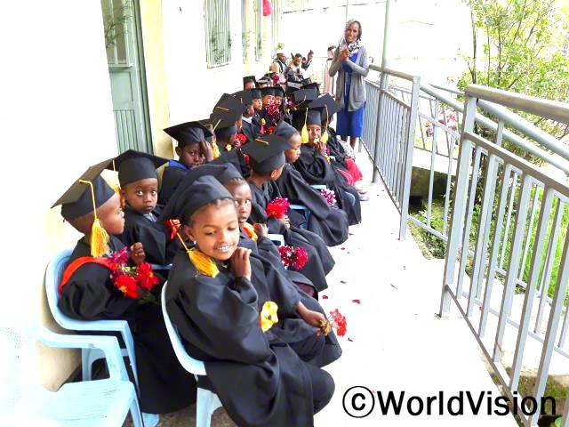 월드비전에서 마을에 유치원을 지어주기 전까지만 해도, 마을 아이들 대부분은 유치원에 다니지 않았어요. 지금은 아이들이 유치원에서 읽기, 쓰기, 수학 실력을 키워서 다음 반으로 올라가거나 유치원을 졸업한답니다. - 자라 (유치원 교사)년 사진
