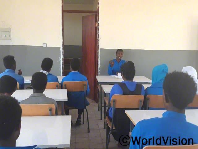 """""""월드비전의 도움으로 학교에 아동의회가 생겼고 현재 59명의 학생들이 위원회로 활동하고 있습니다. 아동의회가 생긴 이후로 많은 아동보호문제가 해결되었답니다."""" –고사(16세)년 사진"""