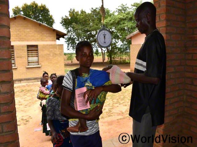 """""""마을 아이들의 건강 증진을 위해, 함께해 주시는 후원자님께 감사드려요. 예전에는 한 번도 아이들을 병원에 데려온 적이 없었는데, 5세 미만의 아이들의 건강검진 중요성을 배우고 나서, 아이들과 함께 병원에 방문하고 있어요. 정말 감사합니다."""" - 말리타(23세)년 사진"""