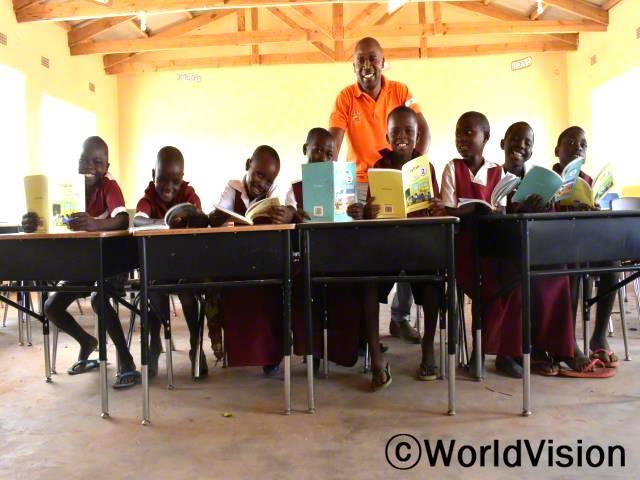 """""""전에는 허름한 건물에서 수업을 했는데 비가 오는 날이면 물이 새서 수업을 제대로 할 수 없었어요. 하지만 월드비전의 도움으로 교실이 생겨서 이제는 비가 와도 아이들이 안전하게 수업을 들을 수 있게 되었답니다."""" –치소모(학교 선생님)년 사진"""