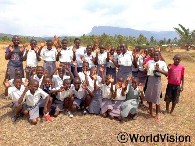 우간다 나만요니 지역개발사업장 팀장 마리 헬렌 아콜 씨와 지역사회 아동들의 모습입니다.년 사진