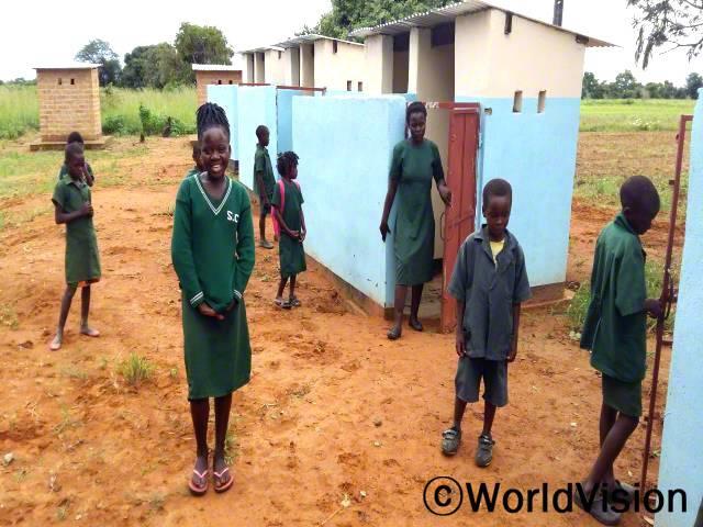 저는 취약한 위생방안을 사용하였고 숲 속에서 일을 보곤 했어요. 하지만 이제는 깨끗한 화장실을 사용하고 식수대도 사용할 수 있어요. -므웬다(10세), 가운데 웃고있는 아이년 사진