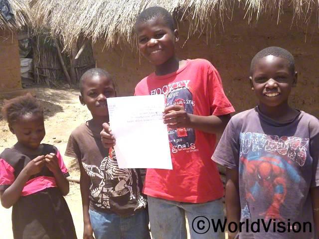 페일드(빨강색 티셔츠를 입은 아동)는 독서 캠프에서 글로 이야기를 쓰는 법을 배웠습니다.년 사진