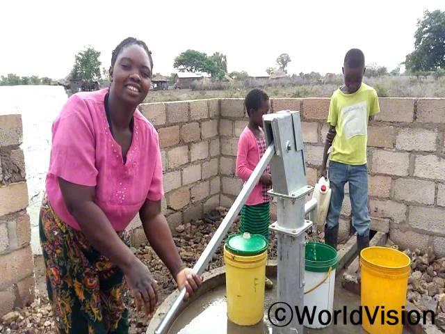 """""""전에는 강에서 길은 물을 마셔서 설사병에 걸리곤 했는데 월드비전의 도움으로 마을에 수도시설이 생겨서 깨끗한 물을 쓸 수 있게 되었어요. 덕분에 아이들은 더 이상 아프지 않고 매일 학교에 갈 수 있게 되었답니다."""" –페비(39세)년 사진"""