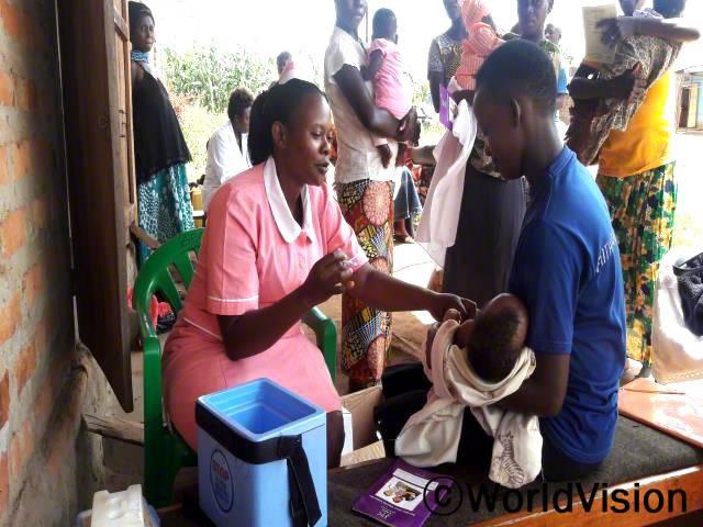 예방접종을 맞는 곳이 멀리 떨어져 있어서 그동안 아동들이 소아마비나 홍역과 같은 질병에 걸렸어요. 이제 매달 의료진이 우리 마을에 방문해 예방접종을 놔주어서, 아동들이 질병으로부터 안전하게 되었어요. -아주나(엄마, 파란색 티셔츠를 입고 있는 사람)년 사진