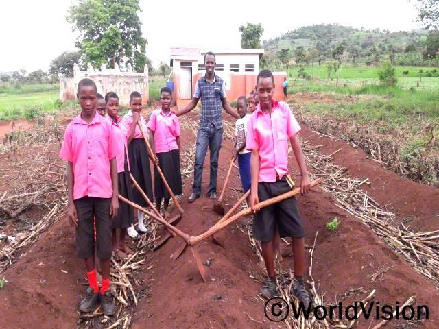 우간다 카킨도 지역개발사업장 팀장인 엠마누엘 아코리모와 지역사회 아동들의 모습입니다.년 사진