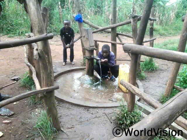 """월드비전이 마을에 수도시설을 설치해 준 덕분에 아이들은 더 이상 물을 길으러 먼 길을 걸어갈 필요가 없게 되었습니다. """"집 근처에 수도시설이 생겨서 공부할 수 있는 충분한 시간이 생겼어요."""" –네버트(11세, 물 펌프에 서 있는 아동)년 사진"""
