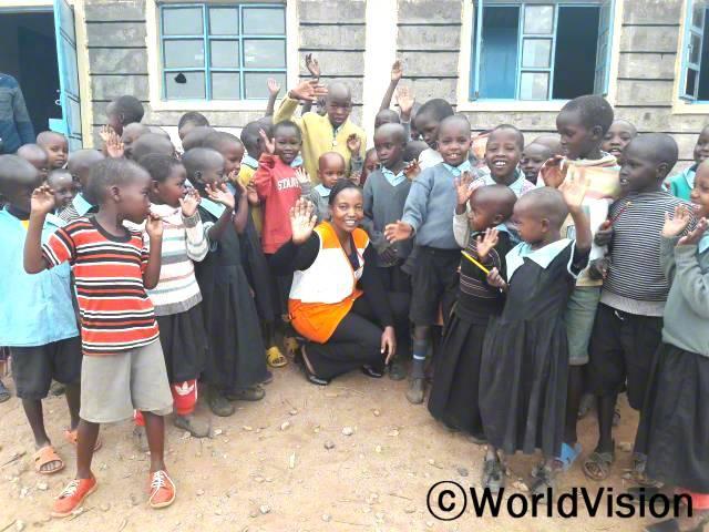 케냐 오실리기 지역개발사업장 팀장 타비타 음완기 씨와 지역사회 아동들의 모습입니다.년 사진
