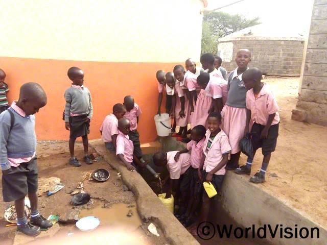 물이 부족해서 학교에서 먼거리를 걸어다니며 물을 찾아다녀야 했어요. 이제 학교에서 새 물탱크가 생겨서 감사하고 가까이에서 깨끗한 물을 사용할 수 있게 되었어요. -시파토이(12세, 회색 스웨터를 입고 서 있는 아동)년 사진