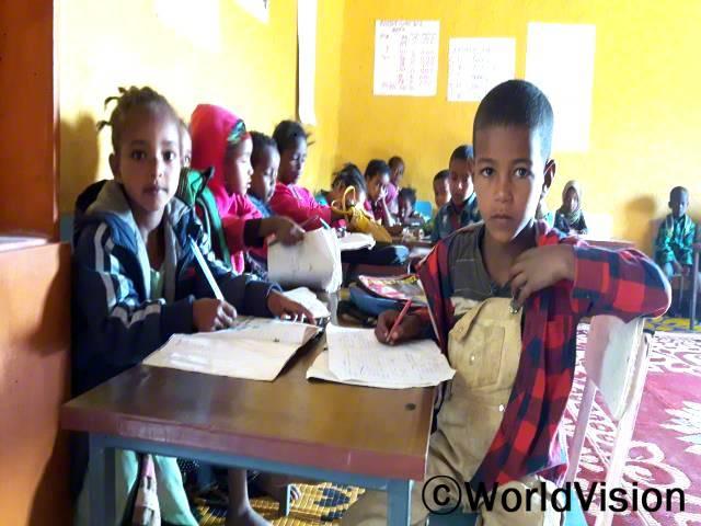 새 유치원에서 공부할 수 있어서 행복해요. 이제 재미있고 흥미롭게 공부할 수 있는 공간이 생겼어요. 숫자와 알파벳을 배울 수 있고 행복해요. -무아즈(6세, 빨간색 체크무늬 셔츠를 입고 있는 아동)년 사진