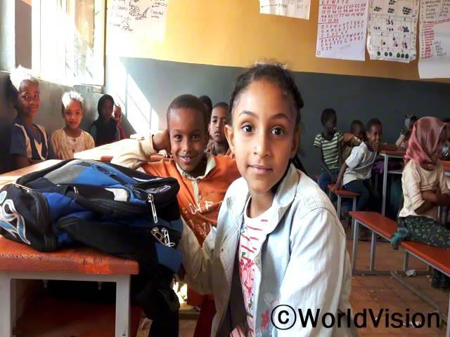 전에 사용하던 교실은 지금처럼 편하지 않았어요. 지금은 책상도 새것에 교실도 새로 지어진 교실이에요. 교실이 밝아진 덕분에 수업에 더 집중할 수 있어요. -콘지트 (9세, 3학년, 맨 앞에 있는 아동)년 사진