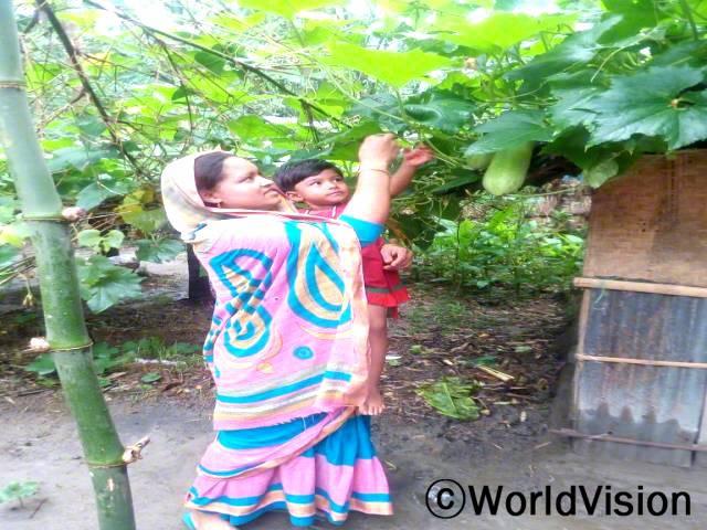 텃밭에서 호박을 수확하게 되어 모니(27세)는 정말 기쁩니다. 월드비전에서 교육도 받고 호박씨도 제공받아 앞마당에 심었습니다. 호박나무 덕분에 아이들에게 영양가 있는 음식을 먹일 수 있게 되었습니다.년 사진