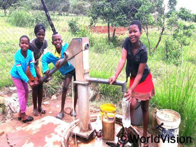 새로운 수도시설은 우리에게 깨끗하고 안전한 물을 공급해요. 이제 우리는 먼 거리에서 물을 길러오지 않아도되며 공부할 시간이 늘어났어요. -아넬레(11세), 검은색 셔츠를 입은 아동년 사진