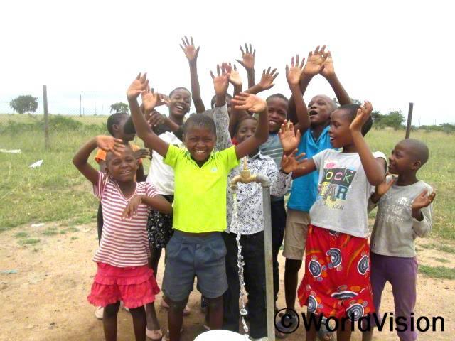 예전에 더러운 물을 마실 수 밖에 없을 때는 종종 몸이 아팠어요. 새로운 식수시설이 생긴 다음부터는 학교에서도 깨끗하고 안전한 물을 마실 수 있게 되었어요. -세투(8세, 가운데 노란색 셔츠를 입고 있는 아동)년 사진