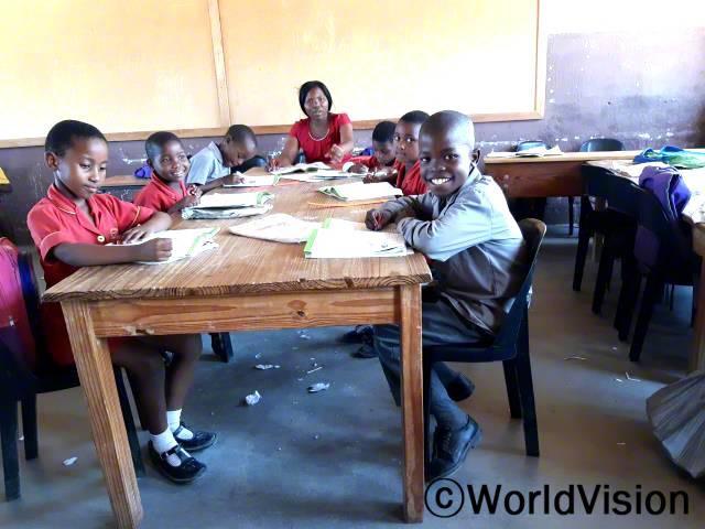 """""""전에는 교실에 의자가 없어서 벽돌이나 바닥에 앉아 수업을 들어야 했는데 월드비전이 의자를 지원해준 덕분에 편하게 앉아서 수업을 들을 수 있게 되었어요."""" –알완데(제일 오른쪽 아동)년 사진"""