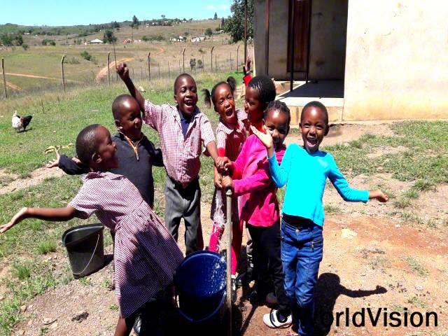 예전에는 집에서 멀리 떨어진 곳에서 길어온 더러운 물을 마셔야 했어요. 이제 집 가까이에서 깨끗한 물을 마실 수 있게 되어 행복해요. 이제 더이상 먼 거리를 걸어서 물을 길어오지 않아도 돼요. -아넬레(10세, 가운데 회색바지를 입고 있는 아동)년 사진