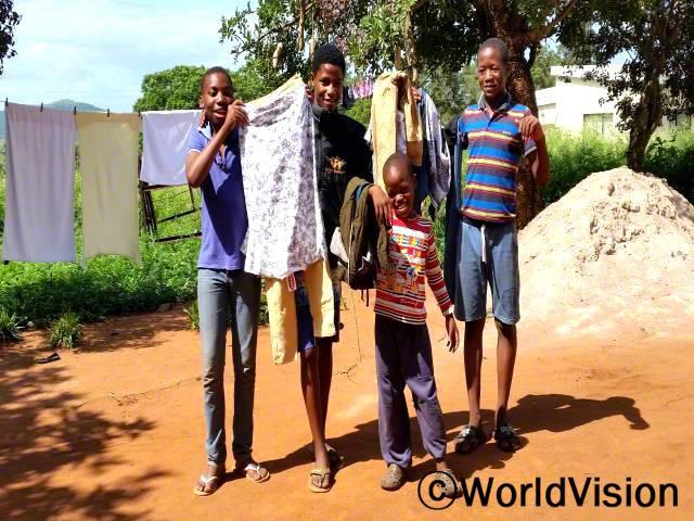 만디사(13세, 검정색 티셔츠를 입고 있는 아동)는 저축에 대해 배운 후 새 옷을 살 수 있게 되어서 행복합니다.년 사진