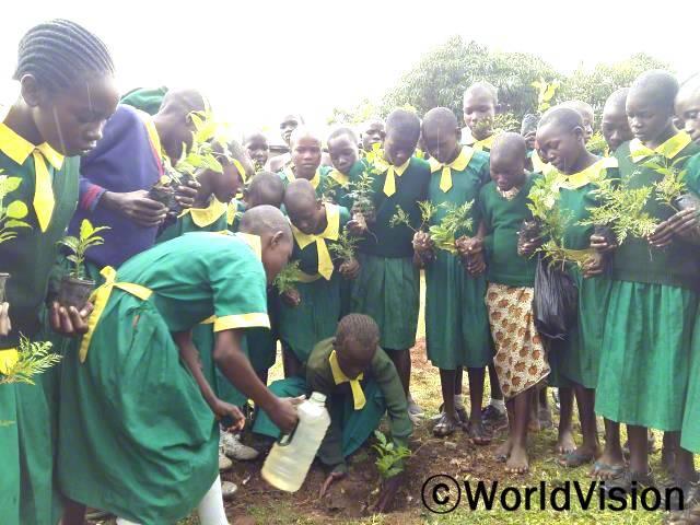 저는 이제 나무를 베지 않을거에요. 나무는 자연환경을 보존해요. 저희 학교에게 나무를 선물해준 월드비전에게 감사해요. -할리마(11세), 중앙에 서있는 아동년 사진