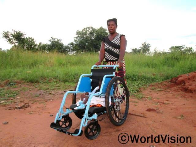 """후원자님의 도움으로 월드비전은 4개의 휠체어를 신체장애가 있는 아동들에게 기증했습니다.한 장애아동의 어머니, 미니바씨(28세)는 말합니다. """"이전에는 우리 아들이 보건소를 갈 때 항상 제가 등에 업고 가야 했는데 이제는 휠체어에 태워 훨씬 더 쉽게 이동할 수 있게 됐어요. 정말 기쁩니다.""""년 사진"""