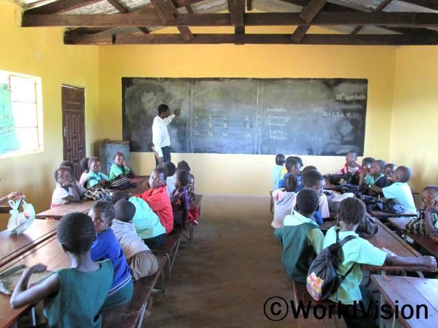 """월드비전은 파트너들과 협력해 지역사회 학교에 새 교무실과 교실을 세워주었습니다.""""어린 학생들의 입학률이 높아졌고 교사도 꾸준히 확보되고 있어요. 어린 아이들의 글을 읽고 쓰는 능력도 전반적으로 많이 향상되었어요.""""라고 학교 교사인 험프리씨(38세)는 말했습니다.년 사진"""