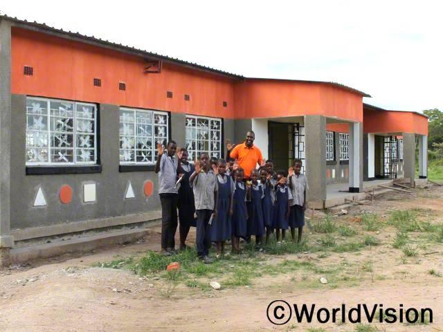 교육사업월드비전은 우리가 공부할 수 있도록 새로운 교실을 지어줬어요.- 모세, 12세 (왼쪽, 검은 바지를 입은 아동)년 사진