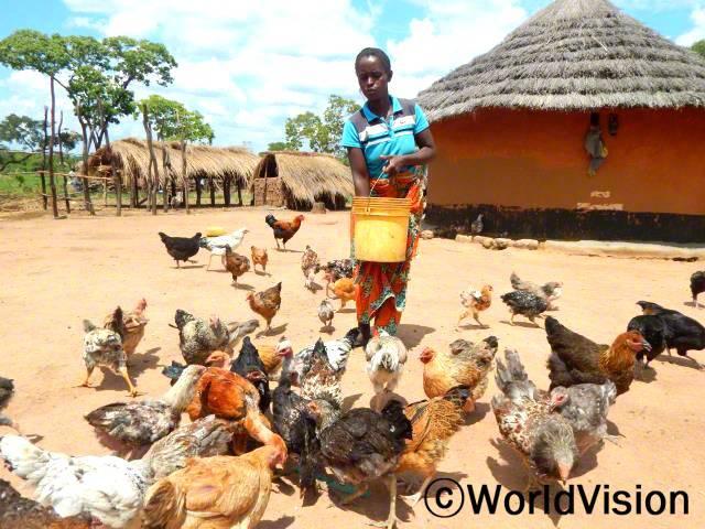 새로운 사업을 통해, 가족들이 기본적인 생활을 유지할 수 있게 되어서 감사해요. - 체리티(모, 닭 모이를 주고 있는 사람)년 사진