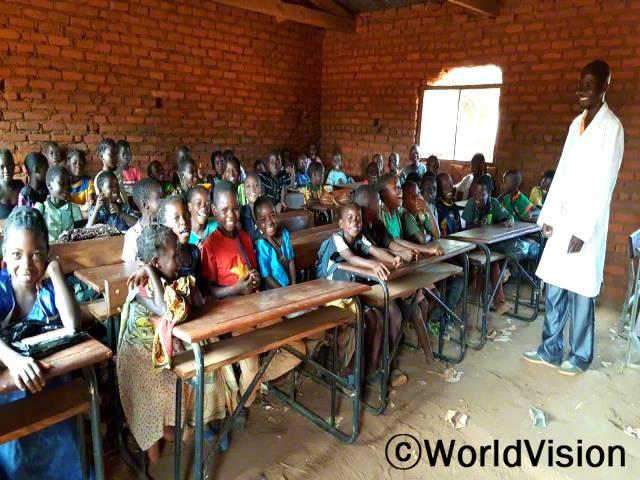 학교에 책상과 의자가 생겨서 저는 학교 가는게 좋아요. 이제는 바닥에 앉지 않아도 되고 공부도 잘 할 수 있어요. -토마스(11세, 빨강색 티셔츠 입은 아동)년 사진