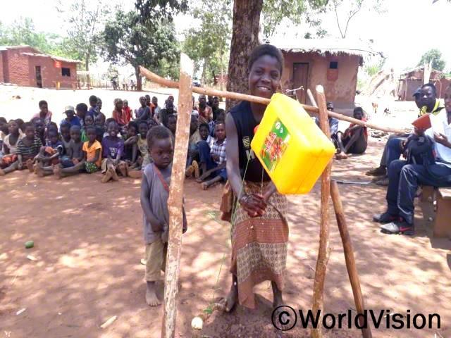 """""""주변 마을 주민들과 다같이 간이 세면대를 활용해 위생 교육을 받았어요. 전염병을 예방하려면 손을 잘 씻어야 한다는 걸 배웠어요."""" -시텔리아(12세)년 사진"""