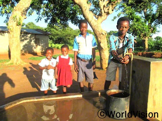 마을에 수도관이 생기고부터는 수인성 질병에 걸리는 경우가 줄었어요. 그리고, 어린 아이들도 어려움 없이 물을 뜰 수 있게 되어 기뻐요. -야미카니(14세, 오른쪽에 있는 아동)년 사진