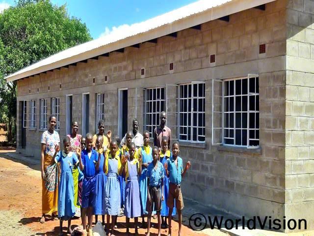 """""""월드비전의 도움으로 학교에 새로운 교실이 생겼어요. 덕분에 전보다 더 많은 아이들이 학교에 입학했고 수업의 질도 향상되었답니다."""" –카팔라물라(학교 선생님)년 사진"""